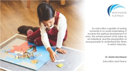Primary aged girl on floor carpet with Montessori map material